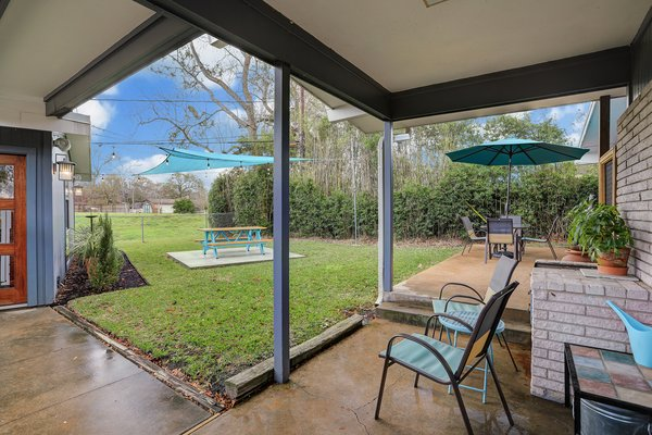 A peek at the covered patio located at the back of the house. With no rear neighbors and a fenced backyard, the property, which sits on an over half-acre lot, offers ample privacy.