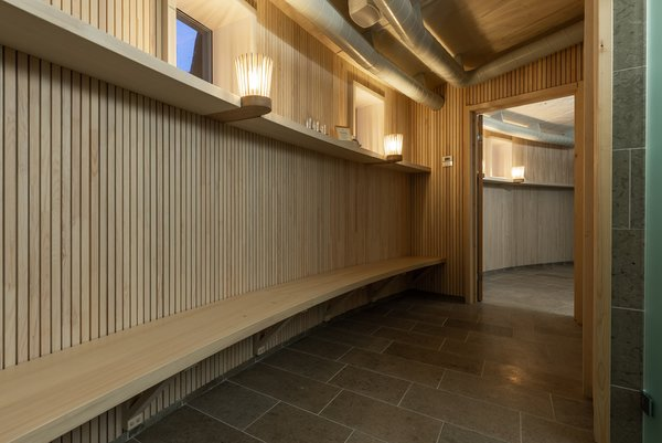 The bath's interiors are lined with beautiful slatted wood, accent lighting, and tile floors.