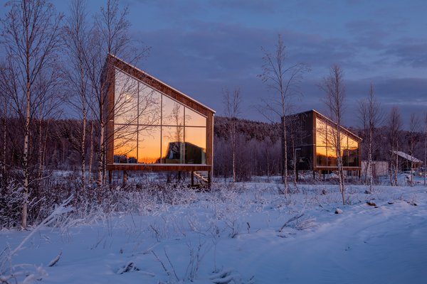 The land cabins are built on stilts to avoid the need to shovel snow all season. Floor-to-ceiling windows grant breathtaking views of the region's remarkable setting.