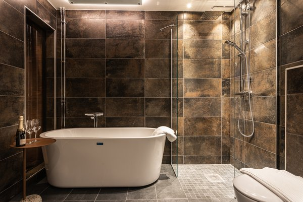 Each bathroom has a shower, a toilet, a standalone bathtub, and a sink. Champagne awaits your arrival.
