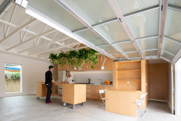 Working with Prismática Architects, Losada-Amor designed the main space to serve multiple functions. In the kitchen, a table drops down for dining or work, and a rolling island can be moved as needed.
