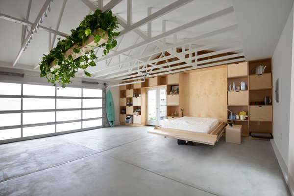 """Shelving in the living area holds storage as well as a Murphy bed for guests. """"It's like a Swiss Army knife,"""" says Losada-Amor. """"Everything is a tool that you can fold or slice."""""""