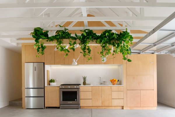 """""""It doesn't feel like a garage because Ramiro cut away the boxiness, but we could still roll a car in here,"""" says Jorge. The refrigerator is by Haier; the range is by KitchenAid."""