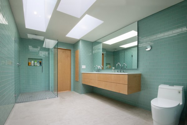 """Skylights illuminate the bathroom, which sits in the center of the unit and is elevated slightly to accommodate the plumbing below. """"It's a wood box on the exterior and glass on the interior,"""" says Ruben. """"It feels open and serene."""" The glass tile is from Arizona Tile. The sink is from Toto."""