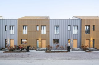 The homes with a north-south orientation feature silver facades. Wooden slats are affixed to every other residence for visual variation.