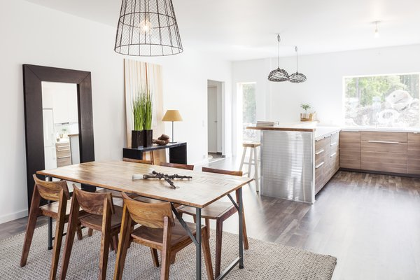 The homes' interiors are open and airy. The ground-floor kitchen opens to the dining room, which leads to the the living area. There, two sets of glass doors provide access to a terrace, expanding available living space.