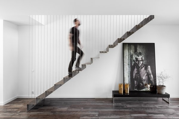 Metal stairs attached via wires allow an abundance of light to reach the first floor.