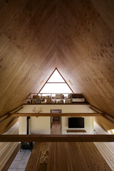 The view from the opposite end, where an additional loft area is used as the children's bedroom. Plywood ceilings complement the hardwood floors below.