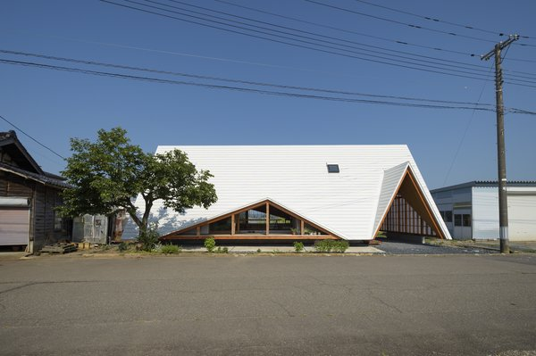 Takayuki Shimada of Takeru Shoji Architects designed this A-frame residence in the rural village of Tsurugasone, Japan. A tent-like white steel roof tops the home, which mixes private spaces with a semipublic, open-air living and dining area.