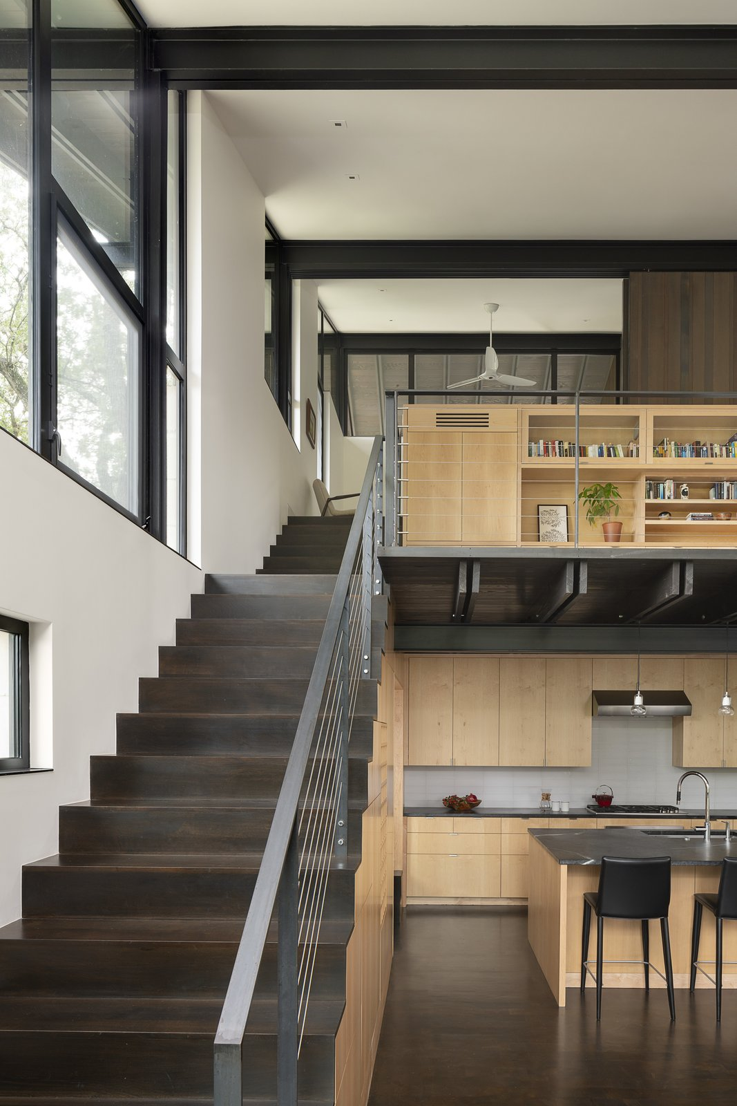 Staircase, Wood Tread, and Metal Railing Upstairs, there's a second-floor office and work by the homeowners' daughter, artist Kat Marais.  Photos from This Spectacular Texas Retreat Cascades Down a Wooded Hillside