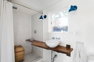 In the bathroom, a custom-designed oak vanity extends into the large, penny-tiled shower.