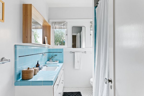 Original blue tile lines the counter and backsplash in one of the two bathrooms.