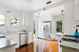 A quaint breakfast nook, complete with an L-shaped bench sits the corner opposite a door leading outside.