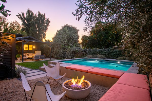 Designed by Foundation Landscape Design, the concrete pool surround also features built-in seating that wraps around a fire pit.