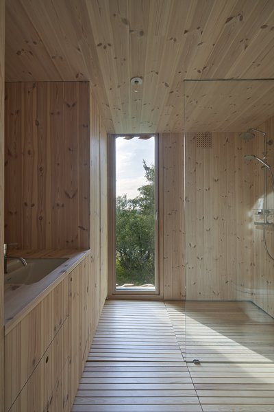 The master bathroom is encased in wood, from the floors and shower walls, to the vanity and toilet button plate. A small door opens to the outside.