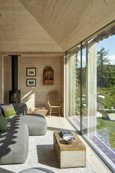 Floor-to-ceiling windows look out onto the woods and meadow surrounding the home. The stove is by Hwam.
