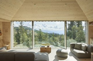 Beyond the facade of rough-cut logs laid out in a diagonal pattern, Casper and Lexie Mork-Ulnes' rural Norwegian home is defined by a material palette of pine, brightened by the natural light and wood and meadow views that pour through the floor-to-ceiling windows.