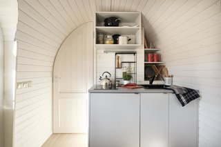 A compact kitchen is custom-built for each space. A curved doorway leads to the bathroom.