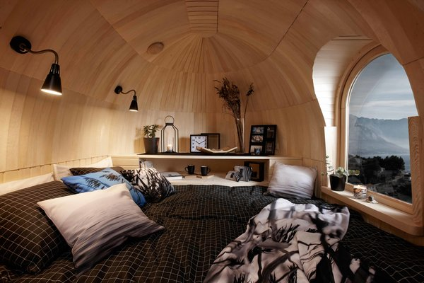 Inside, the cabins are wrapped in either aspen or spruce, with most of the timber sourced sustainably from Estonian forests. The same shingling technique used on the exterior is employed to create a layered, half-dome design at each end of the hut.