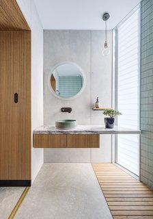 In one of the home's bathrooms, a sink from Lindsey Wherrett Ceramics gracefully sits under a circular mirror from Clearlight Designs. The Ilde Wood S pendant is by David Abad.