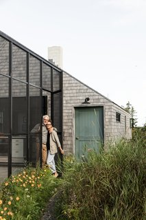 """Berman and Horn outside of their home. <span style=""""font-family: Theinhardt, -apple-system, BlinkMacSystemFont, &quot;Segoe UI&quot;, Roboto, Oxygen-Sans, Ubuntu, Cantarell, &quot;Helvetica Neue&quot;, sans-serif;"""">The front door is painted in Webster Green by Benjamin Moore.</span>"""