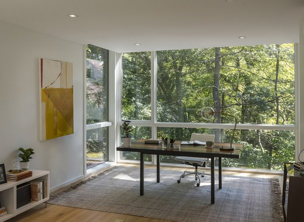 Ed's study—which includes a Jahi Plaid rug by Lauren Ralph Lauren, an Eames chair, and desk lamp by Project 62 for Target—is the only enclosed room on the upper levels.