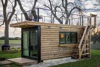 Exterior, Flat RoofLine, Tiny Home Building Type, Prefab Building Type, Wood Siding Material, and Shipping Container Building Type CargoHome specializes in building tiny homes using single-trip shipping containers arriving in the United States from China. Glimpses of the steel structure remain visible around the facade—including the original container doors, which are carved out and inset with new glass panels.