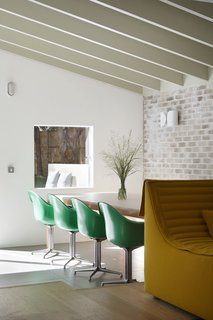 The dining area features Apple Green DAX chairs by Charles and Ray Eames for Herman Miller.