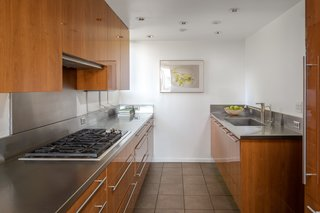 The recently renovated galley kitchen features custom cabinetry, stainless steel counters, and all-new appliances.
