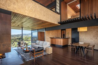 Anchored by a large fireplace, the living room overlooks canyon views from floor-to-ceiling windows. Contrasting cork and redwood paneling is found throughout the space.