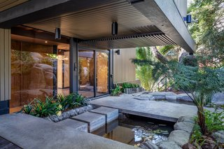 The main entrance greets guests with a koi pond.