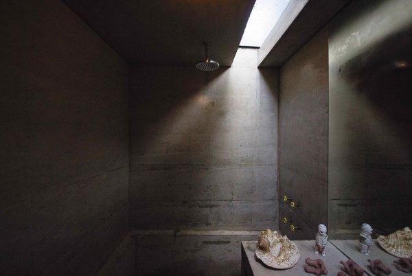 Light penetrates the concrete bathroom via a skylight.
