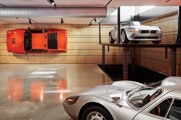 Perhaps the structure's most impressive feature is a wall-mounted BMW M1 hanging in the basement—a carefully completed job that securely bolted the engineless sports car to the wall. A custom lift carries vehicles between the structure's three levels.