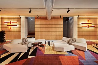 "Another lounge area is located in the sound-proof basement, providing a spot to enjoy the custom stereo system. ""The rug truly captures the '80s love of geometric shapes,"" says Lorenz."