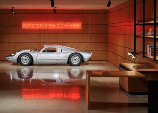 The subterranean level also speaks to the spirit of the design aesthetic, with handsome wood tones and industrial finishes to complement the homeowner's showcase collection of vintage cars. Here, a small study sits alongside a neon-lit Porsche roadster.
