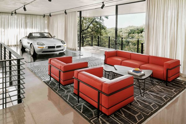 A Le Corbusier sofa and lounge chairs (wrapped in Porsche red leather) complete a seating area on the upper level. Floor-to-ceiling glass wraps around the space, providing views out over the treetops.
