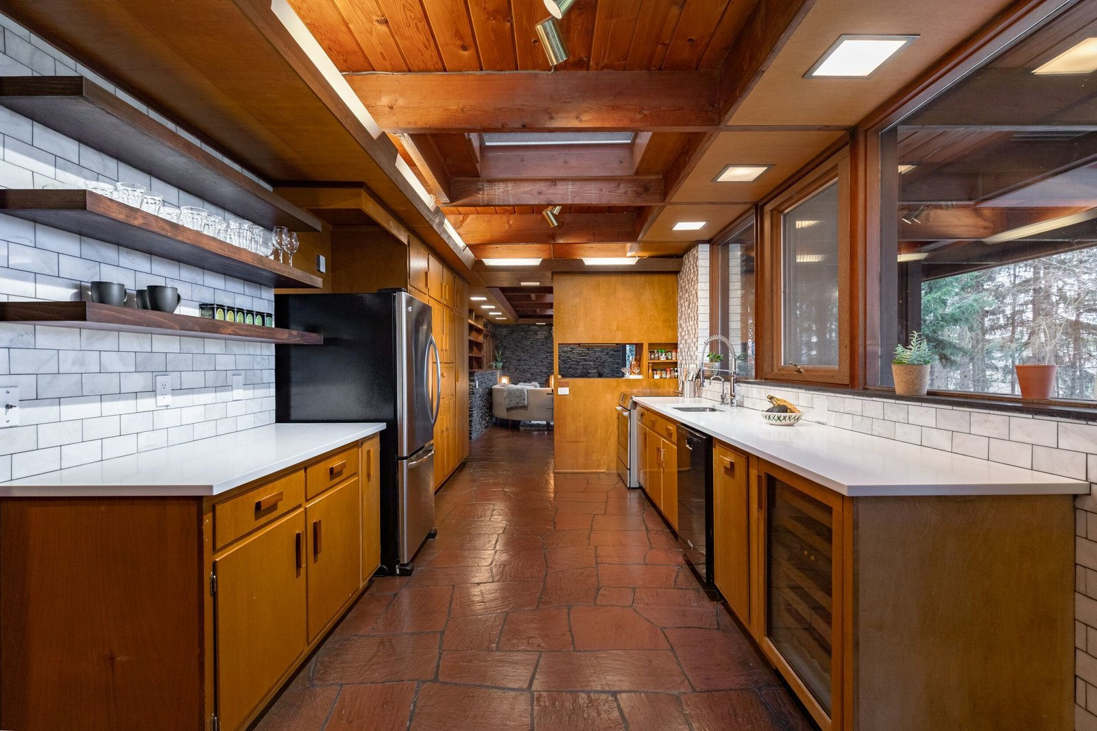 The spacious galley kitchen features original birch cabinetry alongside modern upgrades, including marble subway tile and stainless steel appliances. Windows stretch along one wall, connecting the space with the lush surroundings.  Photo 5 of 8 in A Midcentury Retreat by Architect and Usonia Founder Aaron Resnick Lists for $999K
