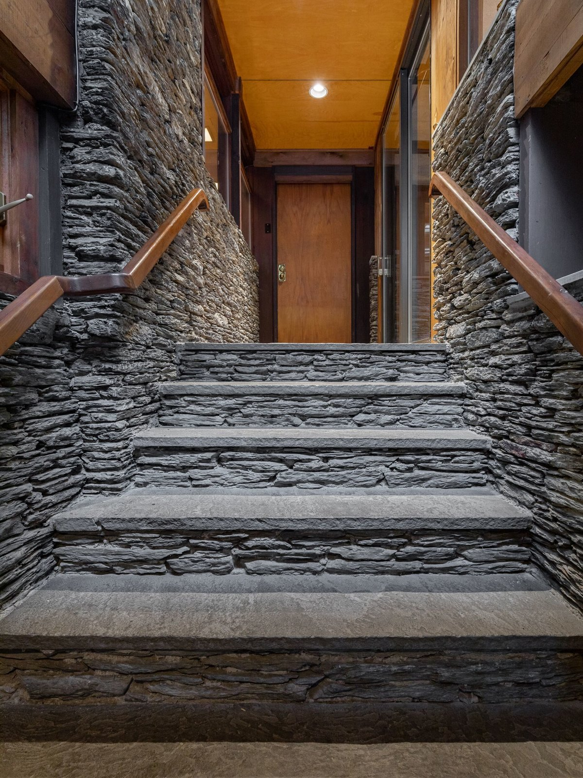 A stone-walled hallway leads to the main living area with walls of glass.  Photo 2 of 8 in A Midcentury Retreat by Architect and Usonia Founder Aaron Resnick Lists for $999K