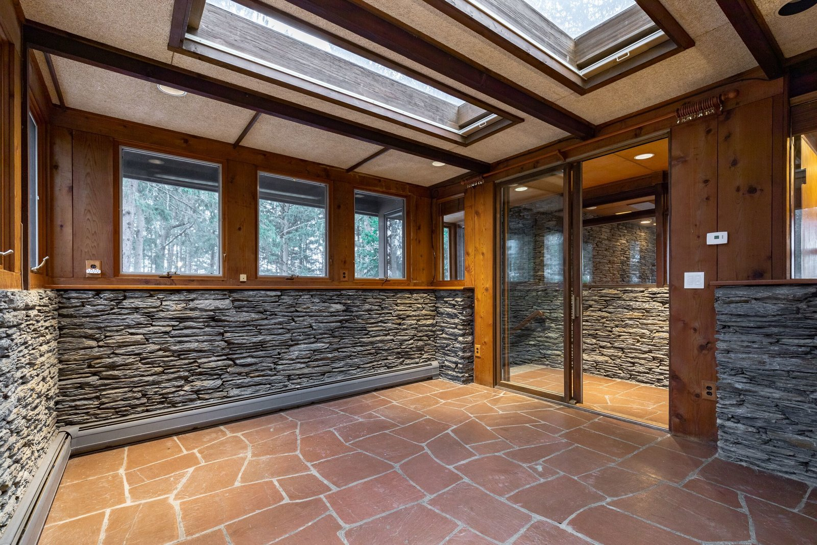 Inside a sunroom, red slate floors contrast with stacked bluestone and wood-clad walls. Natural light pours in from windows surrounding all sides of the space, along with additional exposure from several skylights overhead.  Photo 6 of 8 in A Midcentury Retreat by Architect and Usonia Founder Aaron Resnick Lists for $999K
