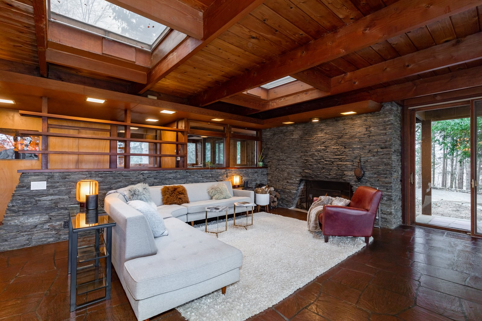 The home's centerpiece is an expansive great room complete with a wall of floor-to-ceiling windows providing a connection to the outdoors. Anchored by a bluestone fireplace, the skylight-lit space also features exposed rafters and original red slate flooring.  Photo 3 of 8 in A Midcentury Retreat by Architect and Usonia Founder Aaron Resnick Lists for $999K