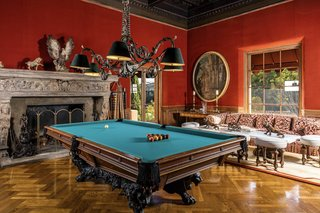 A 32-foot billiards room is lined with herringbone parquet floors. The intricately designed ceiling and carved fireplace are from the Hearst Castle in San Simeon.