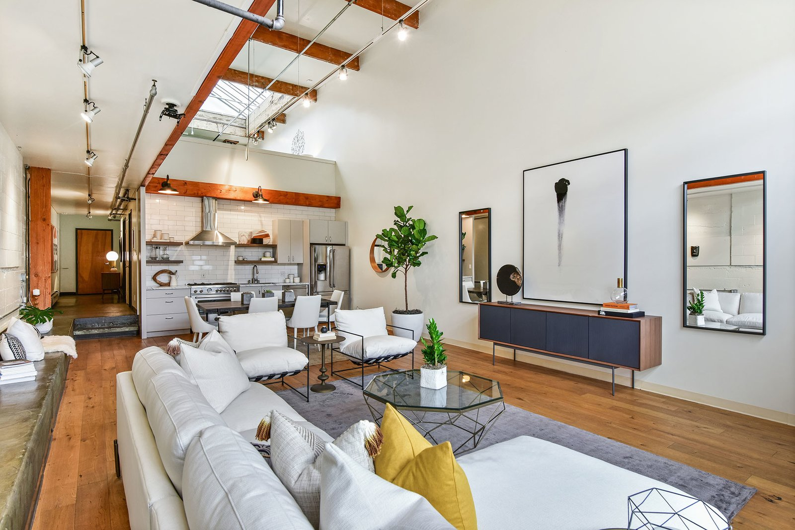 Wide-plank hardwoods line the floor throughout, complementing exposed beams and pillars.  Photo 3 of 9 in A Converted Warehouse Loft in the San Francisco Bay Area Seeks $950K