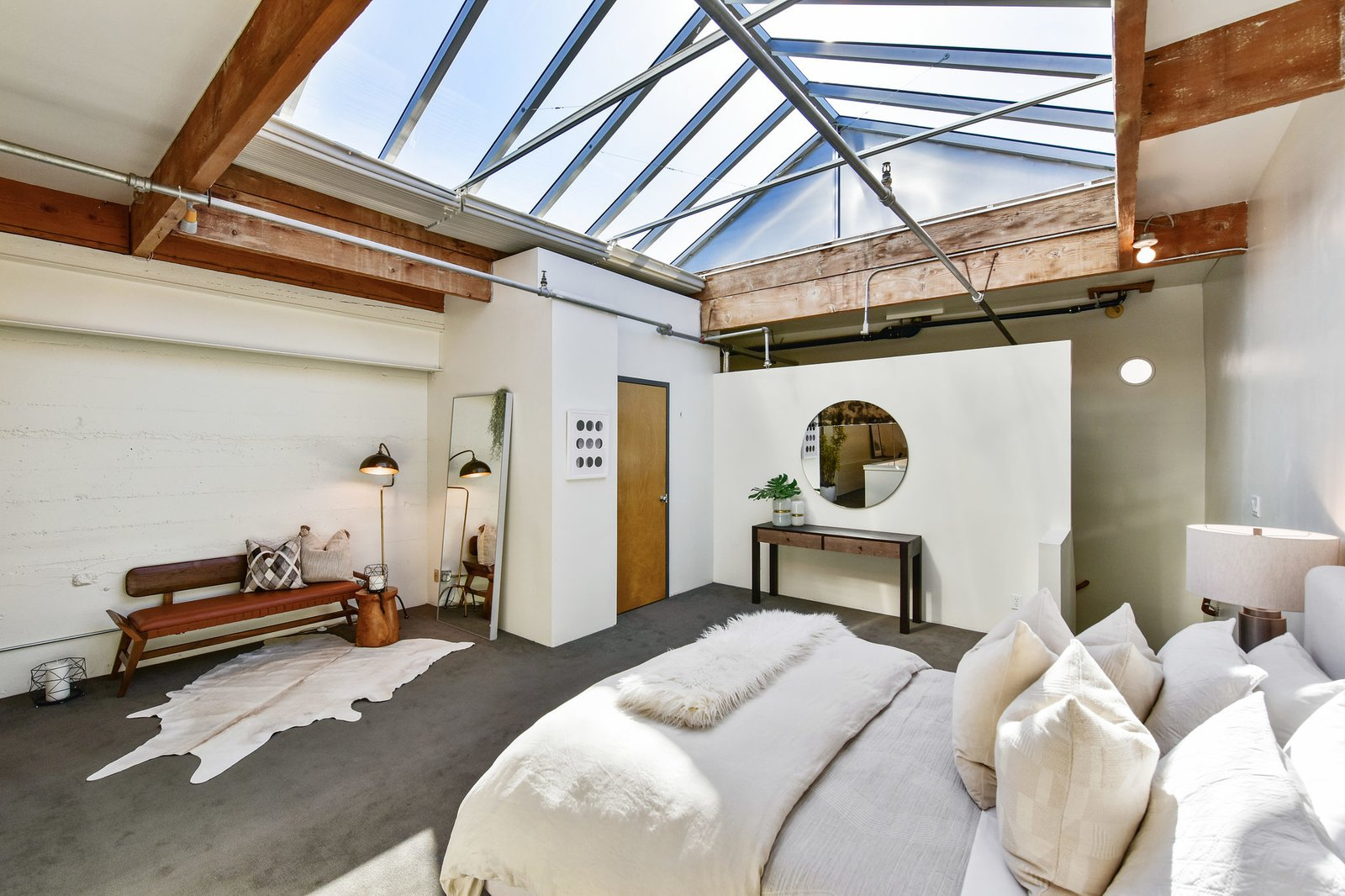 On the upper level, the master suite is illuminated by a massive skylight. A full bathroom is located in the corner.  Photo 6 of 9 in A Converted Warehouse Loft in the San Francisco Bay Area Seeks $950K
