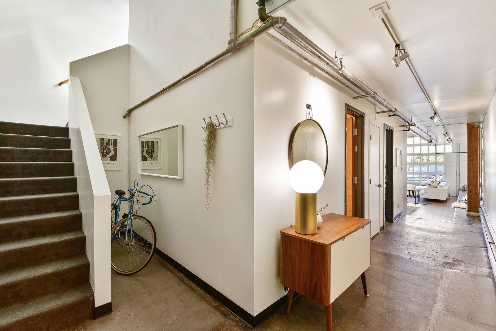 An interior bedroom and a half-bath are located down the hall, as is the home's second entrance. A nook beside the staircase offers space to store bikes.  Photo 5 of 9 in A Converted Warehouse Loft in the San Francisco Bay Area Seeks $950K