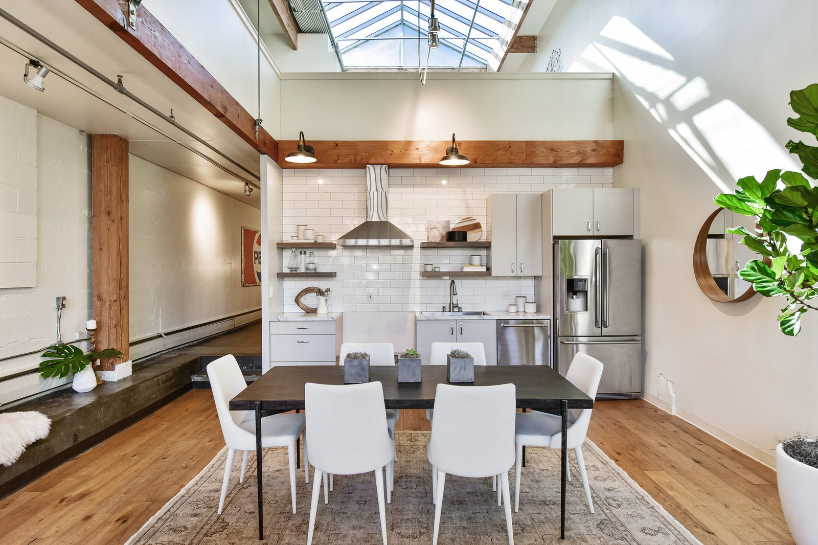 Bright and airy, the updated kitchen features a white subway-tile backsplash and stainless-steel appliances. An open dining area sits connects it with the living area.  Photo 4 of 9 in A Converted Warehouse Loft in the San Francisco Bay Area Seeks $950K
