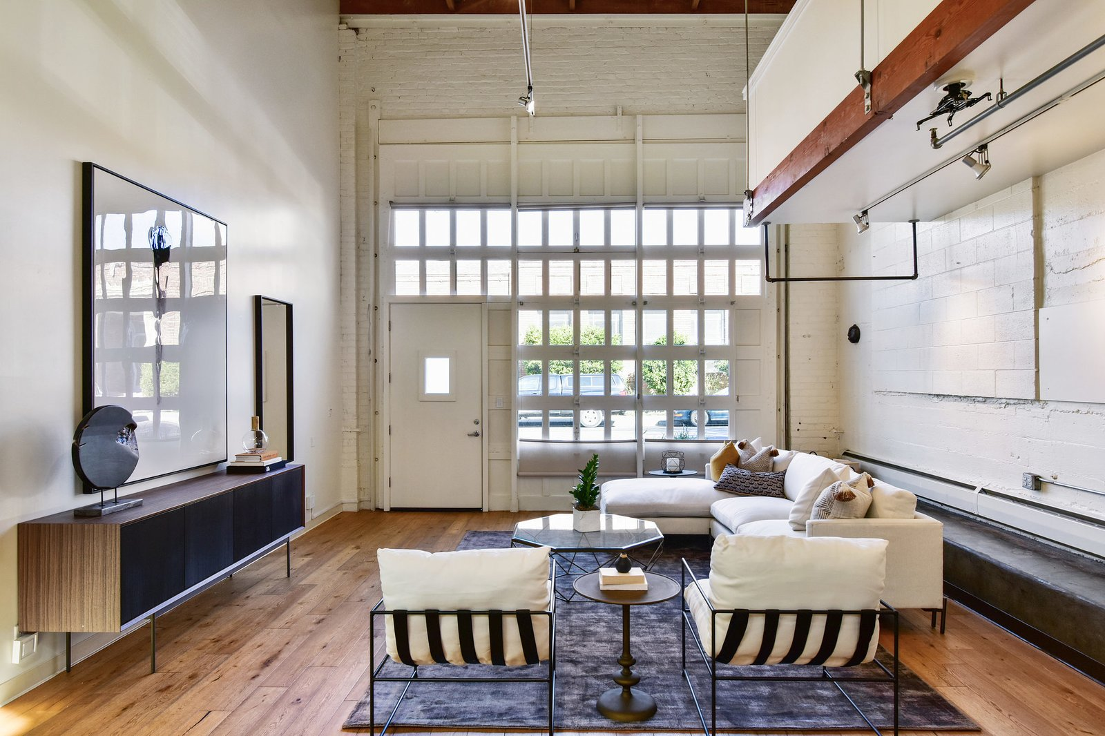 Glass panes on the old garage door bring in natural light. The deep, linear floor plan runs the length of a bay in the old warehouse.  Photo 2 of 9 in A Converted Warehouse Loft in the San Francisco Bay Area Seeks $950K