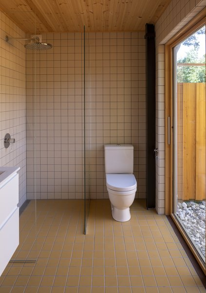 The cabin's single bathroom is located adjacent to the master bedroom and is covered in ocher-colored tile. A fenced-in outdoor bathing area is accessible via a sliding glass door.