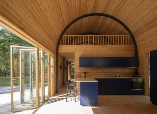 In the kitchen, blue cabinets add a pop of color to the wood-clad interior. Large bi-fold doors intensify the indoor-outdoor connection, extending the living space to the adjacent decking.