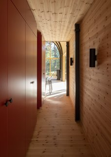 Large cabinets along a corridor underneath the loft provide storage for the minimalist bedrooms.