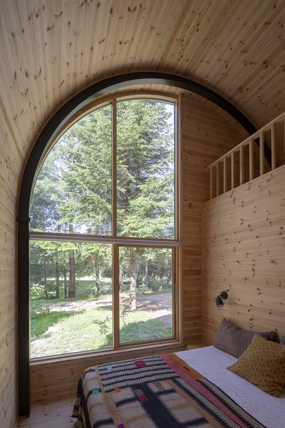 In total, the home features three bedrooms, two of which are tucked underneath the loft. The master bedroom, shown here, is located at the back of the cabin.